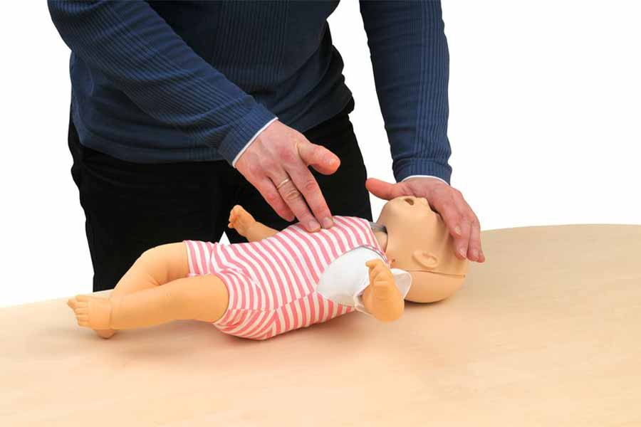 An adult giving CPR to a child sized manakin